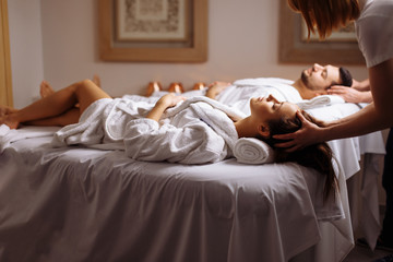 happy young beautiful couple enjoying head massage at the spa