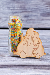 Multicolored candies and plywood rabbits. Colorful sweets in glass jar and couple of plywood bunnies on wooden background. Happy Easter concept.