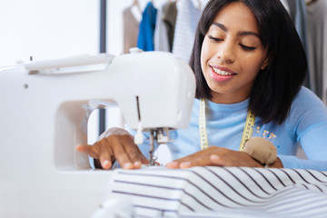 Professional tailor. Qualified experienced cheerful tailor sitting on her working place and making stitches on a lovely striped blouse with a help of a modern sewing machine