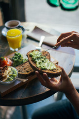 Man spreads avocado on crunchy toasted loaf of bread, breakfast at restaurant or cool coffee spot, with fresh orange juice and other spreads or toppings in background. Enjoy healthy lifestyle choice