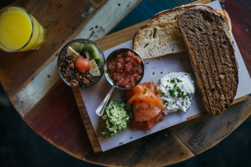 Tasty delicious breakfast or brunch served on wooden board, looks artisan and homemade, crunchy toast with avocado spread, tomato, fresh salmon and philadelphia cheese. with healthy chia pudding