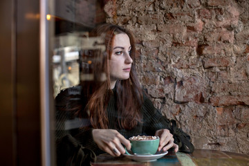 Attractive, pretty young woman sits day dreams in cafe, enjoys drinks coffee or hot chocolate, looks out of window thoughtfull and deep stare. Lonely, not alone, empowered female