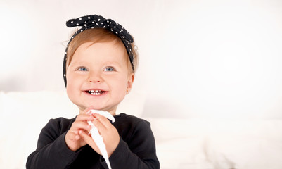 Cute baby girl dressed in a black dress on white light background