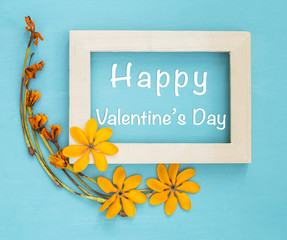 Happy Valentine's day card design, yellow flower on wooden picture frame on blue wooden background