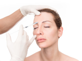 Close up of hands of cosmetologist injecting botox in female face. The woman is closed her eyes with relaxation.