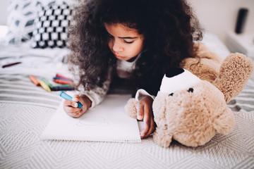 Little girl doing homework on bed at home