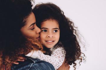 African american mother giving daughter a kiss on cheek Fotoväggar