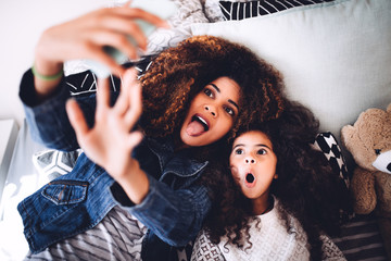 Young mom and daughter taking funny selfie with tablet