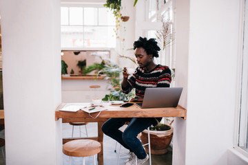 African young man working with laptop in coffee shop