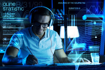 Pleasant music. Cheerful smart enthusiastic programmer having a productive day and listening to his favorite music while sitting in front of a transparent screen and making notes