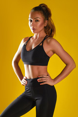 Young happy fitness girl with sporty body posing at studio on a yellow background. Beautiful fit Girl. Fitness model in black sportswear. Weight Loss. Healthy lifestyle. Sporty healthy female.