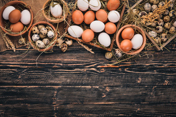 A set of chicken and quail eggs. On a wooden background. Top view. Copy space.