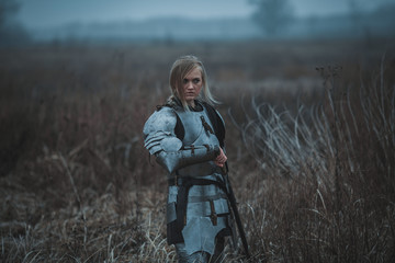 Girl in image of Jeanne d'Arc in armor and with sword in her hands stands on meadow.