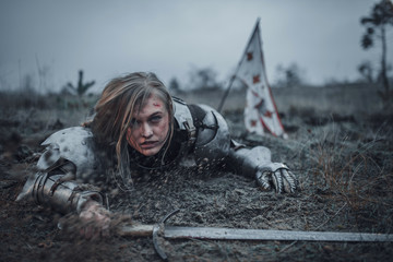 Girl in image of Jeanne d'Arc in armor crawls in mud with sword in her hands on background of flag.