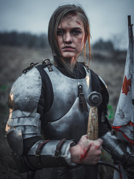 Portrait of girl in image of Jeanne d'Arc in armor with flag and sword in her hands on meadow.