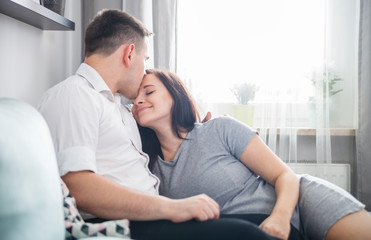 Cheerful pregnant couple relaxing at home and enjoying pregnancy time