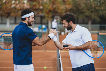 Two young men handshake after a tennis match on a clay court