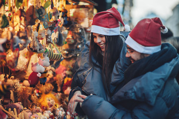Rear view of couple on christmas market looking at decorative to
