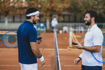 Two young men after a tennis match on a clay court