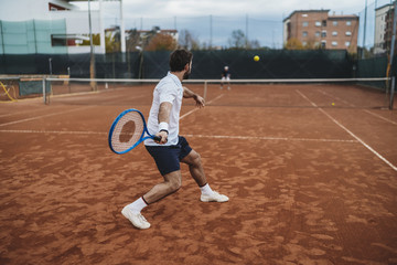 Two young men playing tennis on a clay court