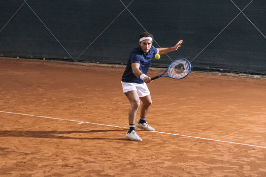Young man playing tennis on a clay court