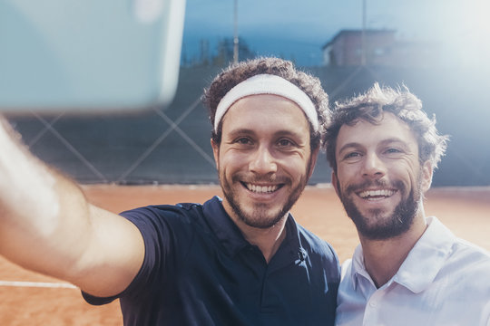 Two young men take a selfie after a tennis match on a clay court