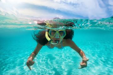 Frau mit Taucherbrille beim Schnorcheln in tropischen Gewässern, halb und halb Aufnahme