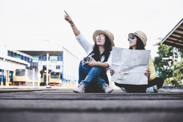 Tourist asian lifestyle friends women wearing backpack holding map, traveler siting for waiting a train, so happy and relax for summer day, Travel Concept.