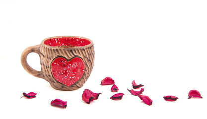 Valentine's Day still life. Clay cup with a red heart and rose petals on white background.