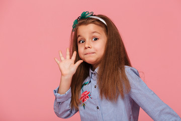 Portrait of funny female kid having long auburn hair looking on camera giving high five meaning hi or bye with hand over pink background