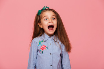 Joyous female kid in trendy shirt having fun shouting being excited and emotional over pink background