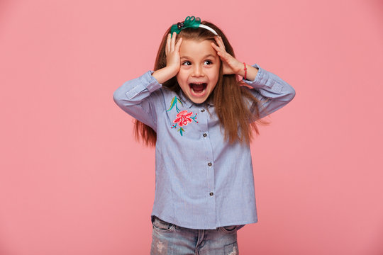Beautiful little girl reacting emotionally grabbing head with both hands being delighted and shocked over pink background