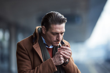 Portrait of serene man lighting up cigarette while locating in street. Tobacco concept