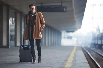 Wall Mural - Full length portrait of serene man waiting for train while keeping big baggage. Travel concept. Copy space