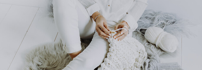 pretty blond young woman sitting on wooden floor and crocheting with white wool