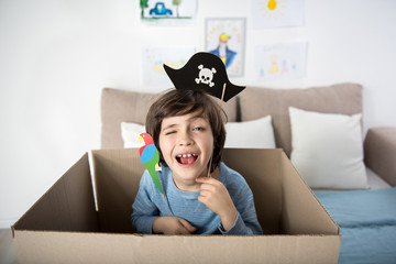 Ahoy. Portrait of funny kid with paper parrot and pirate hat, boy is hiding inside of carton box and winking at camera cheerfully