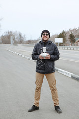 A young man in a jacket operating drone with remote control. Blue sky in the background, a winter holiday in the mountains.