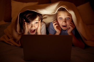Frightened little boys watching film on computer. Kids are lying on bed and their heads covered with blanket Wall mural