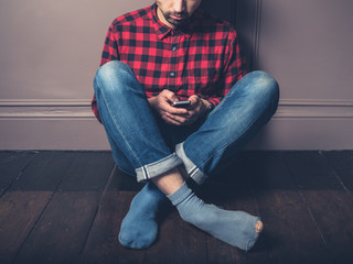Young man with smart phone on wooden floor