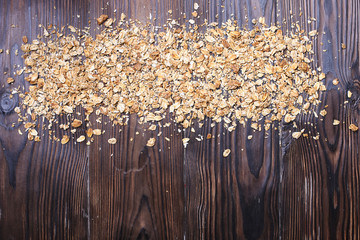 Overhead of granola scattered rolled oats on dark wooden texture table. Healthy nutritious vegan flakes full of carbohydrates and protein for sporty lifestyle. Top view, copy space, background.