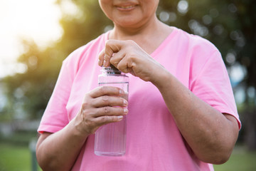 Asian senior Female holding bottle of water.