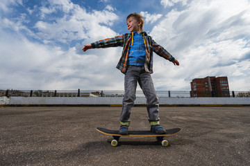 Small boy is going to skateboarding - people, sport and skateboarding concept.