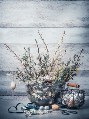 Easter holiday concept with springtime decoration set : bunch of spring branches with cherry blossom, basket with eggs, ribbon and scissors on table at wall background, front view