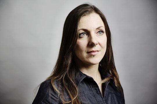 junge Frau mit langem Haar und Piercings im Gesicht, Portrait vor grauem Hintergrund