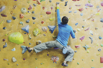 Young man practicing rock-climbing on a rock wall indoors.