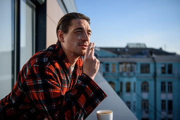 Contented adult male smoking with pensive look. He is standing on the balcony with a cup of coffee. Copy space
