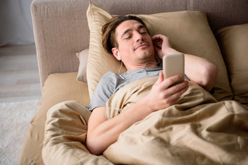 Contented man having rest in bedroom. He is enjoying music with earphones and smiling