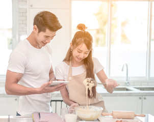 young asian couple happy make bakers helping to make bakery see recipes form tablet