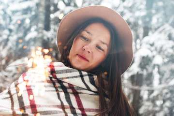 Handsome woman wearing scarf and hat walking in winter forest among snowy trees. Hold belgal light in hand