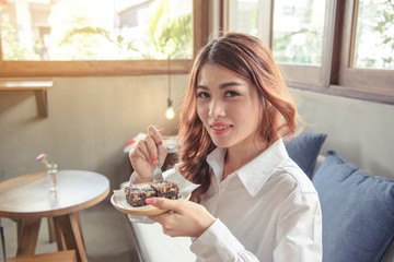 Portrait beautiful young adult woman look cheerful relaxing with dessert while sitting on furniture.